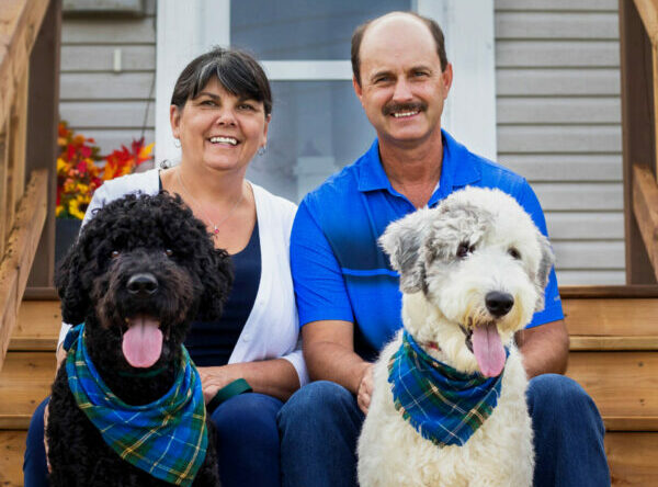 Julie and Brent MacKinnon sit on their step with their two dogs.